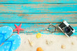 Beach background. Top viwe of beach sand with slipper, starfish,shells, coral, retro camara and bracelet made of seashells on blue wooden background. Summer concept, Vintage retro styles.