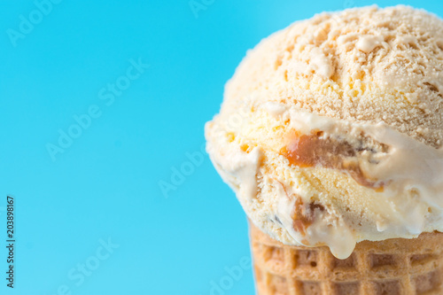 Fotografía Scoop of Delicious Melting Salted Caramel Toffee Vanilla Ice Cream in Waffle Cone on Blue Background