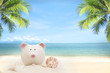 Summer sandy beach with piggy bank and coconut tree on blur ocean and sky background.