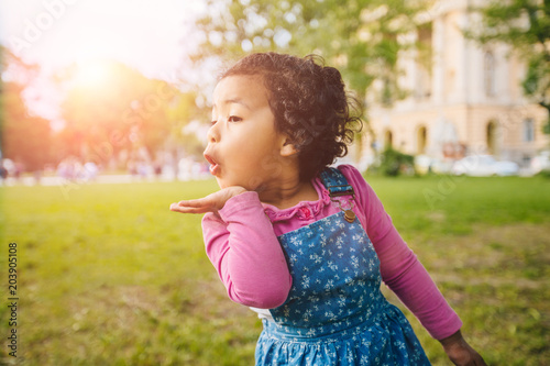 Photo  Cute curly mexican dark skinned toddler baby girl sends an air kiss in european city square