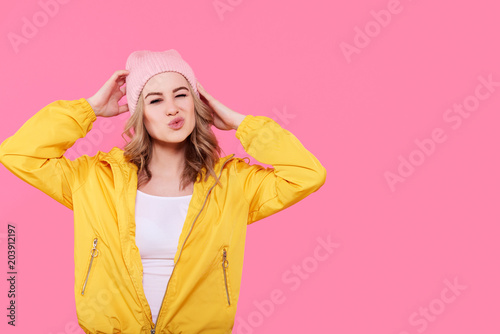 Fotografie, Obraz  Crazy beautiful trendy girl in bright yellow jacket and pink beanie hat puckering lips