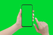 canvas print picture - Woman hands holding phone in vertical position, isolated on green background