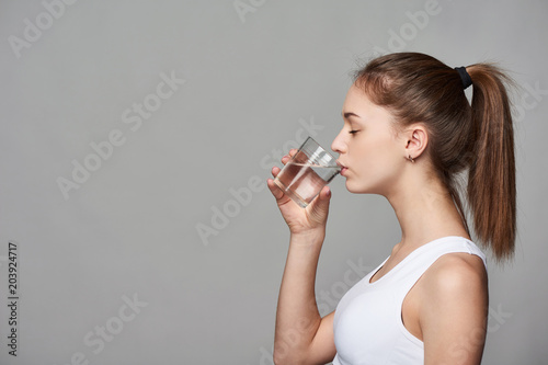 Fotografía  Profile portrait of sporty teen girl drinking clear water with closed eyes