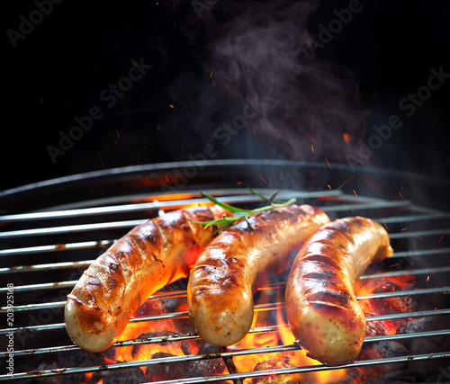 Aluminium Prints Grill / Barbecue Grilled sausages on grill with smoke and flame