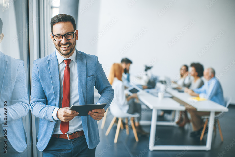 Fototapeta Young businessman with digital tablet in office