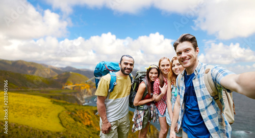 Foto  technology, travel, tourism, hike and people concept - group of smiling friends