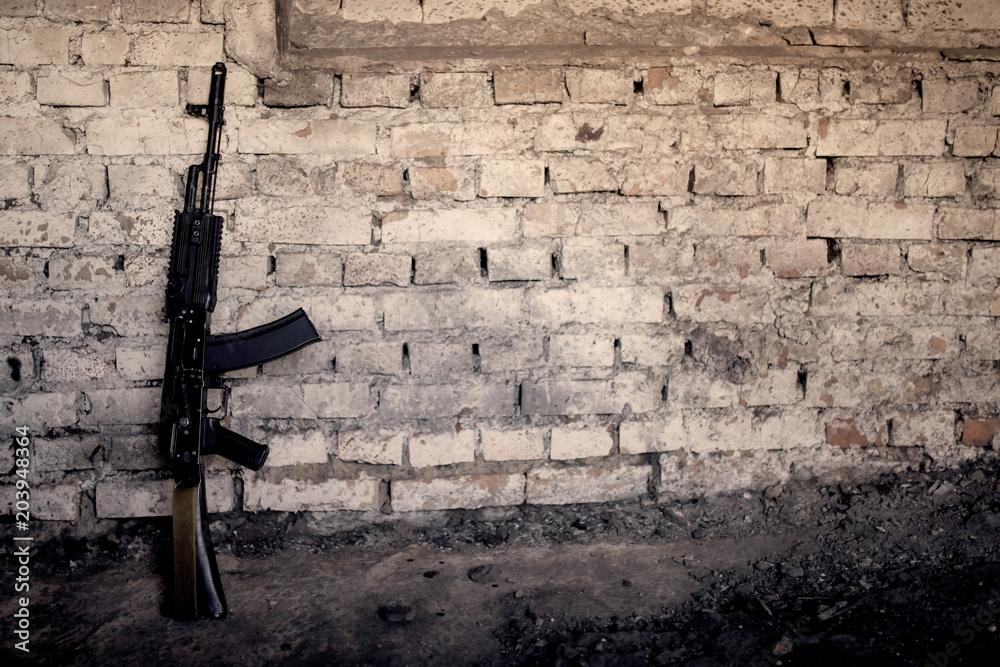 Fototapeta submachine gun kalashnikov AK-47 against the wall