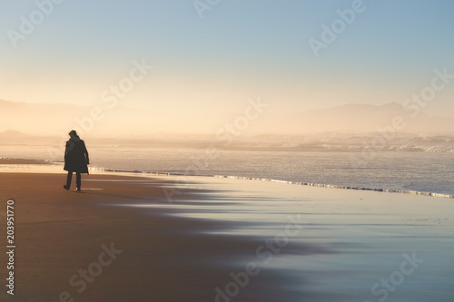 Fotografía  lonely person walking on beach at sunset