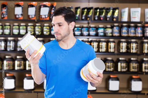 Attractive sport man looking different sport nutrition products