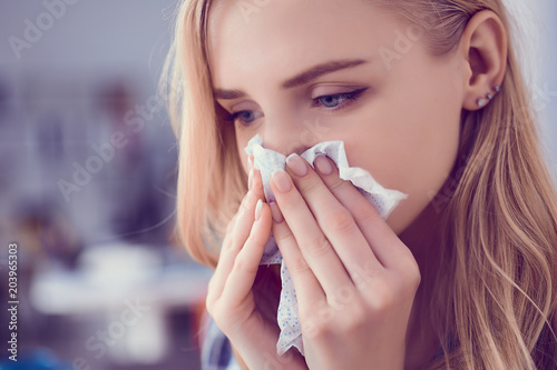 Fotografia, Obraz  Girl blows her nose into a tissue