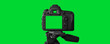 canvas print picture - The Dslr camera with empty screen on the tripod, isolated on green background. The chromakey. Green screen.