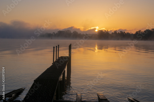 Fotobehang Pier misty sunrise over a lake