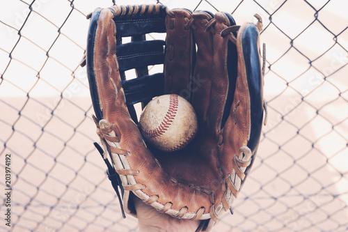 Fotografia, Obraz  American sport of baseball shows closeup of ball in glove from dugout
