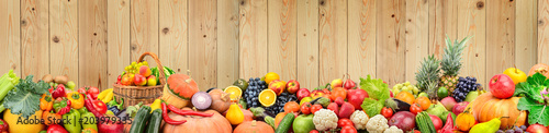 Poster Fruit Panoramic photo healthy vegetables and fruits against light wooden wall.