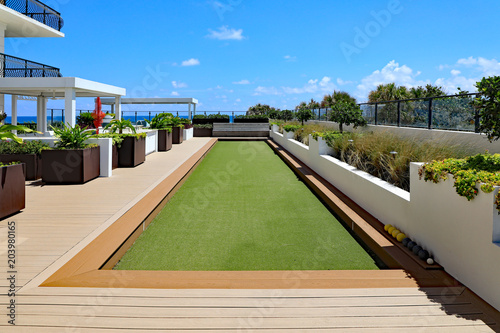 фотографія  Inviting upscale bocce ball court with artificial turf, on a rooftop terrace