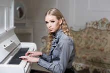 Young Victorian Girl In A Tender Blue Dress Learning To Play Piano. Lovely Blond With Curly Hair Woman Sitting In Room With Vintage Sofa. Private Education Concept
