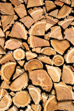 Vertical Photo Of A Dry Chopped Wood, Wooden Logs For A Fire Or A Fireplace Neatly Stacked In A Pile