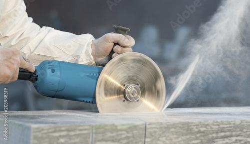 Fotografia Worker cuts stone grinding machine