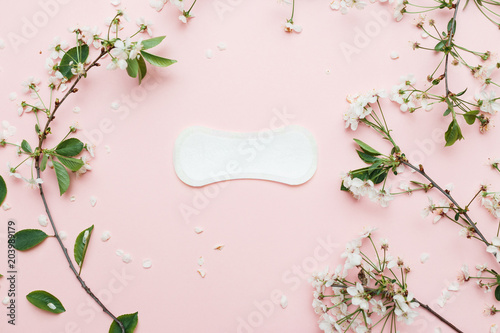 Fotografia  The sanitary napkin lying with blossom on pink background.