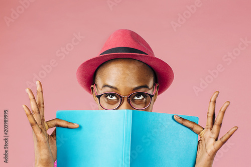 Vászonkép The reader - Portrait of a young woman with glasses holding a book and peeking u