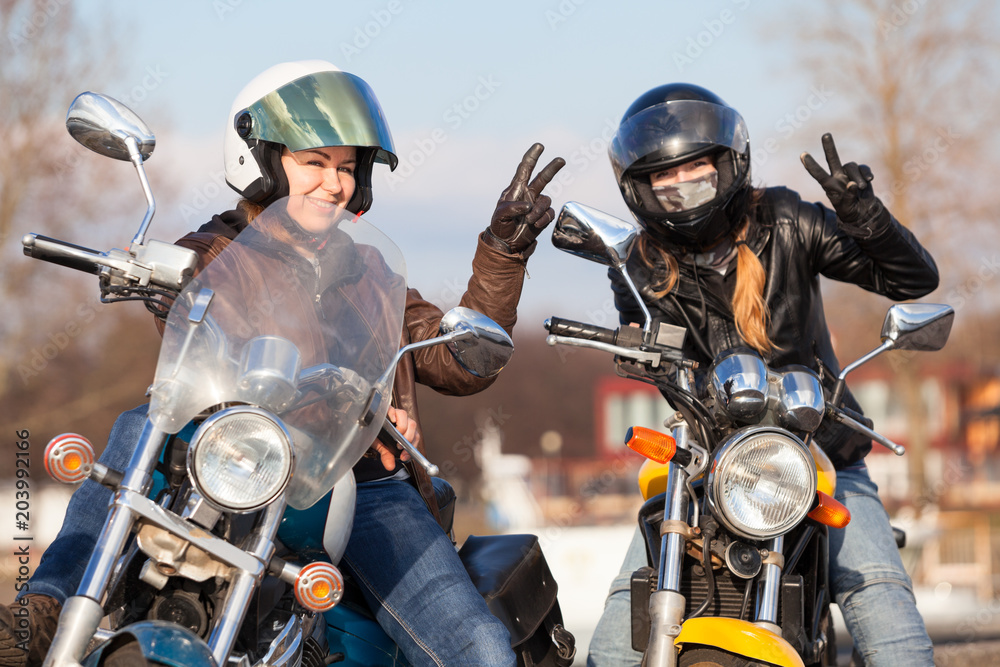 Fototapeta Victory signs in leather gloves from two laughing female bikers with street motorcycles