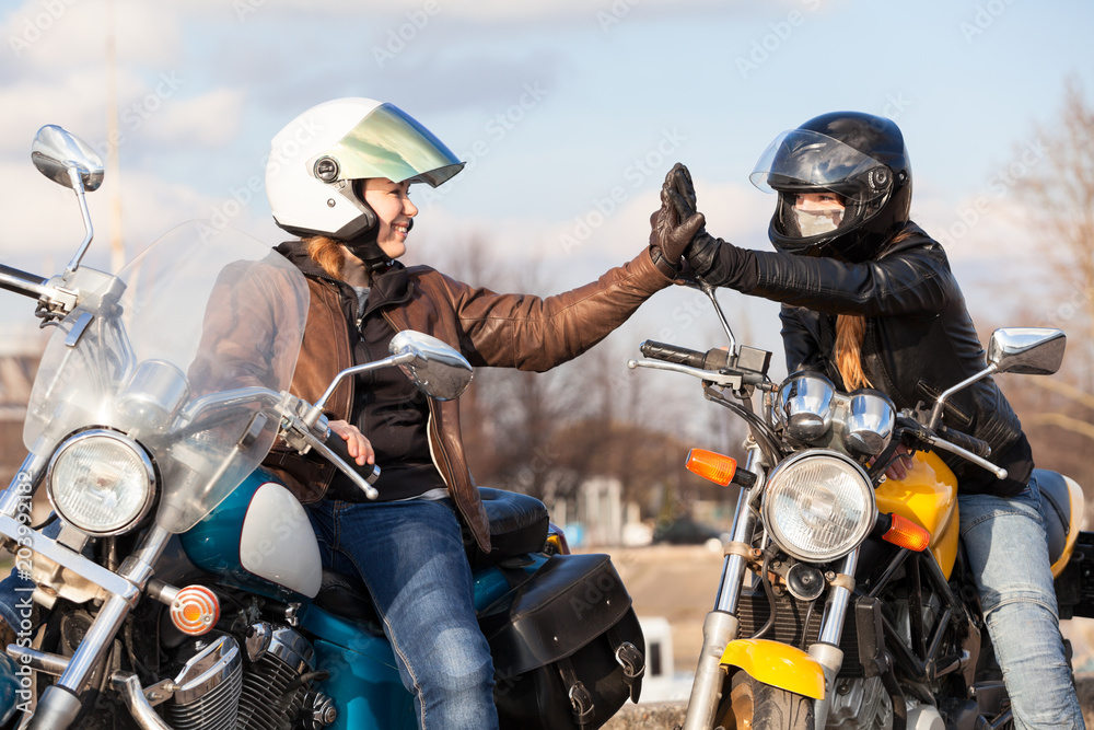 Fototapeta Clapping hands in leather gloves while greeting each other on urban road in partnership