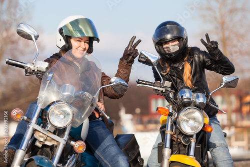 Victory signs in leather gloves from two laughing female bikers with street motorcycles