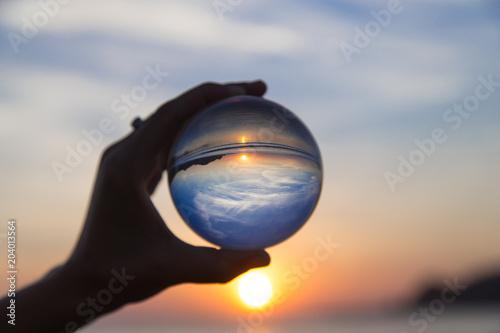 Koncepcja podróży wakacje. Pięknej dziewczyny wisząca kryształowa kula podczas zmierzchu na plaży. Letnia fotografia kreatywna