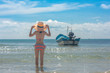 slim woman in bikini holding hat on the head, cheerfully the sea beach enjoyment, with local ferry boat and blue sky in background