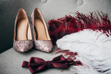 Close Up View Of Bridal Shoes, Grooms Bow Tie And Feathers For Rustic Wedding On Armchair