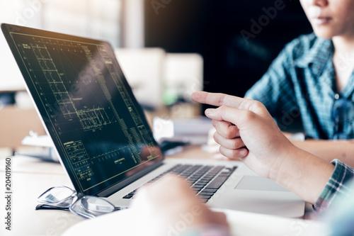 Cuadros en Lienzo Teenagers develop programming with blueprint code in laptop monitor
