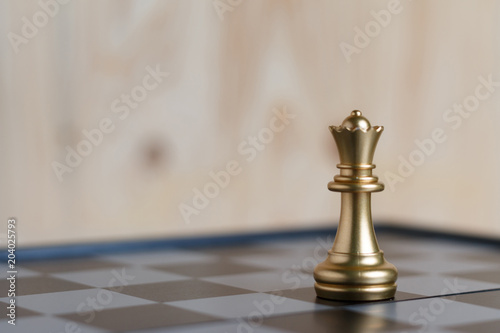 Fototapeta The gold queen chess set on board is located obraz