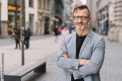 Valokuva  Street portrait of mature man with arms crossed