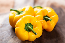 Yellow Bell Peppers Or Sweet Peppers On Wooden Background