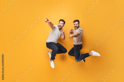 Fotografía  Two young cheerful men jumping together