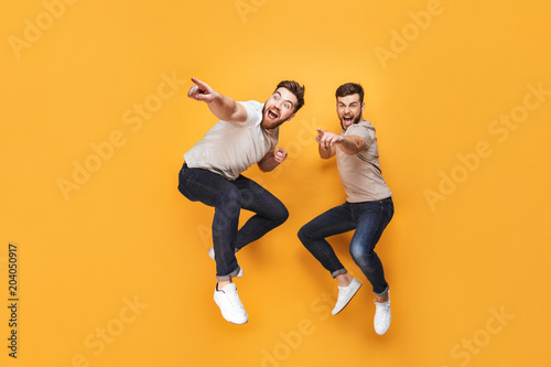 Photo  Two young excited men jumping together