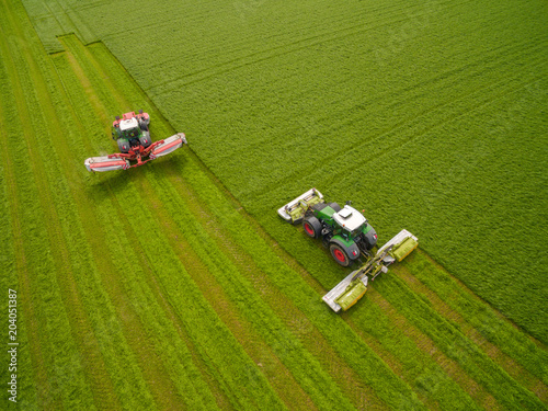Wall Murals Green Aerial view of two tractor mowing a green fresh grass field, farmer in a modern tractors mowing a green fresh grass field on a sunny day