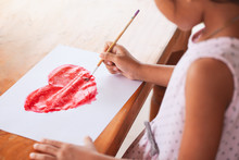 Asian Little Child Girl Drawing And Painted A Heart For Valentine's Card With Fun And Happiness