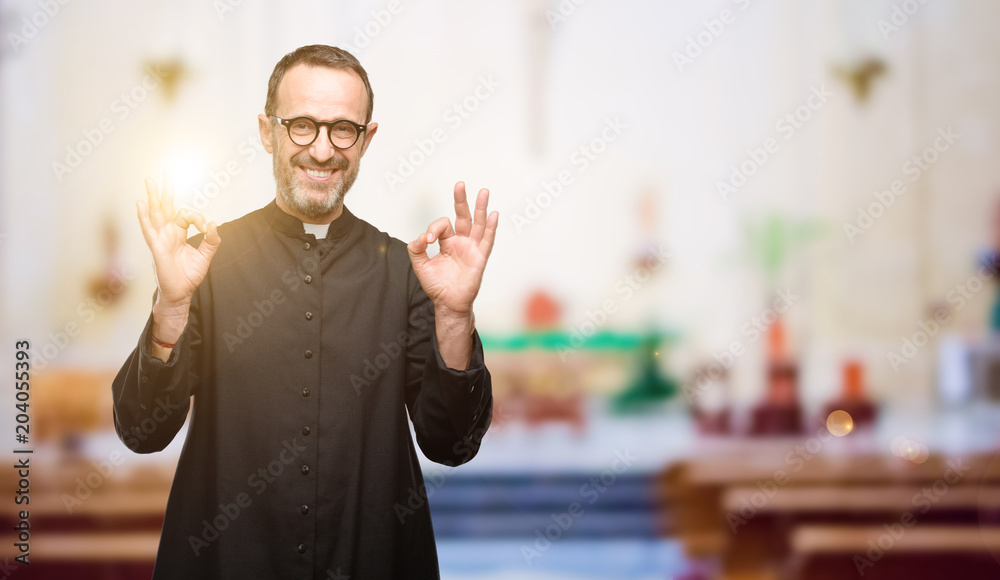 Fototapety, obrazy: Priest religion man doing ok sign gesture with both hands expressing meditation and relaxation at church