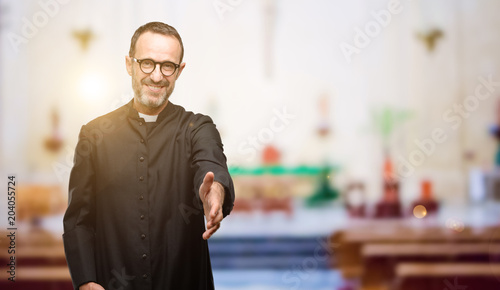 Cuadros en Lienzo Priest religion man holds hands welcoming in handshake pose, expressing trust an