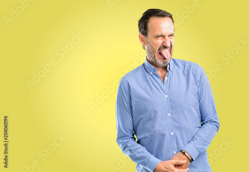 Fotografie, Tablou  Handsome middle age man feeling disgusted with tongue out