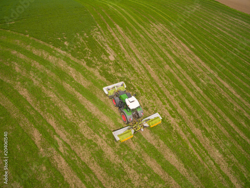 Wall Murals Green Aerial view of a tractor mowing a green fresh grass field, a farmer in a modern tractor mowing a green fresh grass field on a sunny day
