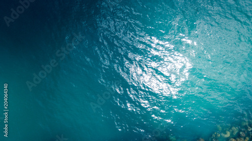 Fotografie, Obraz  Aerial: overhead view of transparent blue sea surface against the coral line and