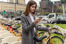Young Stylish Woman Using Bicycle Rent Mobile App Smiling Outdoors, Portrait Of Female Manager Browsing Smartphone Standing Near Bike Sharing To Go Cycling, Concept Of Healthy Lifestyle In The City