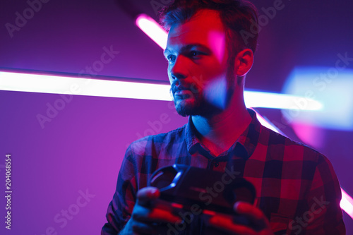 Young man holding VR glasses in neon Slika na platnu