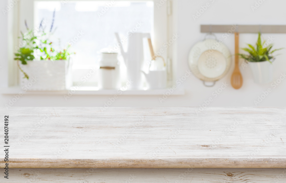 Fototapeta Wooden table top over blurred kitchen interior with copy space