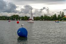Mewa Siedząca Na Niebieskiej Boi Na Jeziorze. W Tle Pływające Jachty