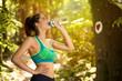 young woman in sportswear drinking water outside