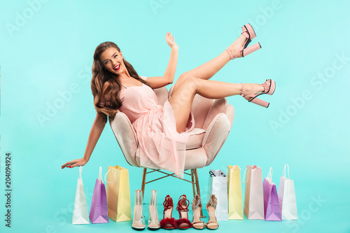Papiers peints Fluvial Portrait of charming woman 20s sitting on pink armchair after shopping with lots of purchase bags, isolated over blue background