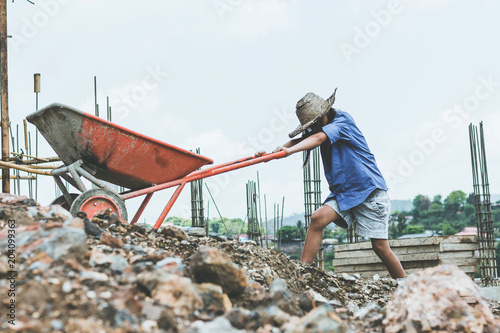 Photo Children working at construction site for world day against children labour conc